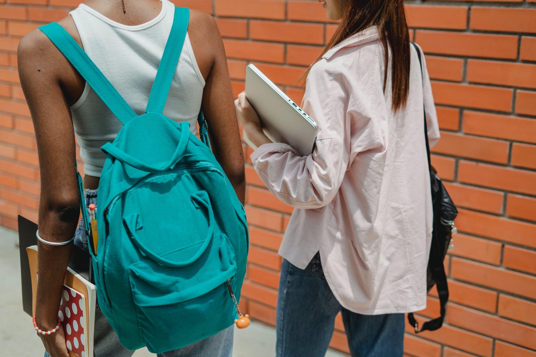 crop faceless multiethnic classmates walking together on sidewalk